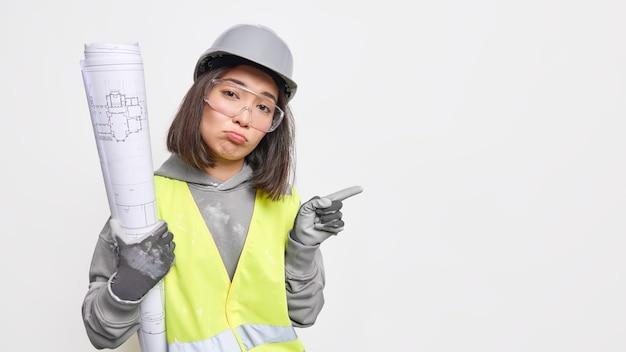 Ingenieurin arbeitet im industriebereich hält blaupause trägt schutzhelmbrille zeigt auf leeren raum für ihre anzeige an.