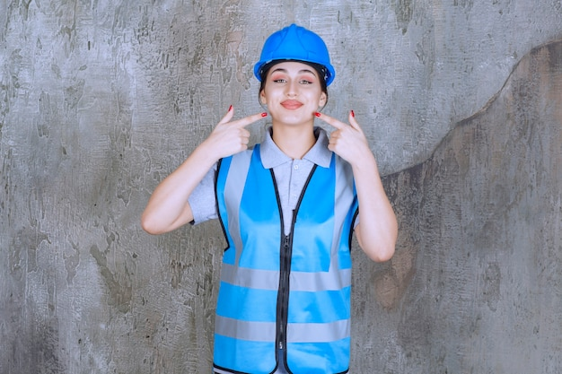 Ingenieurin, die blauen helm und ausrüstung trägt und auf sich selbst zeigt.