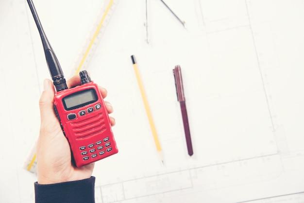 Ingenieurin hält radio in der hand auf der baustelle.