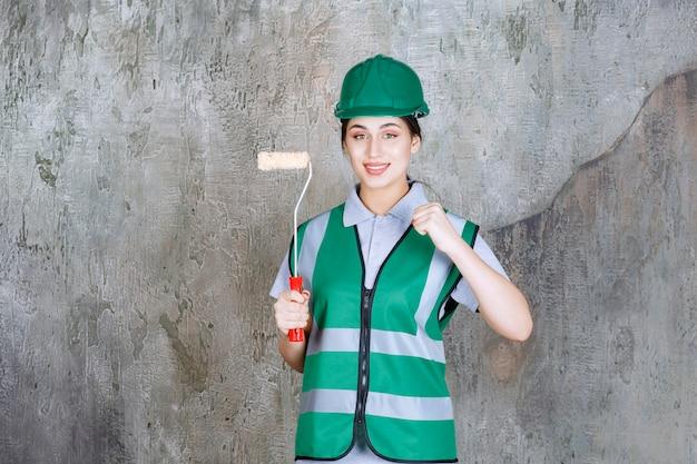 Ingenieurin im grünen helm, die eine trimmrolle für die wandmalerei hält und ein positives handzeichen zeigt.