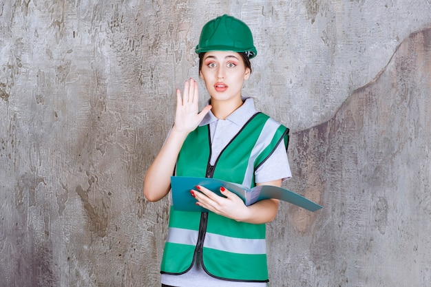 Ingenieurin im grünen helm, die einen blauen ordner hält und etwas stoppt.