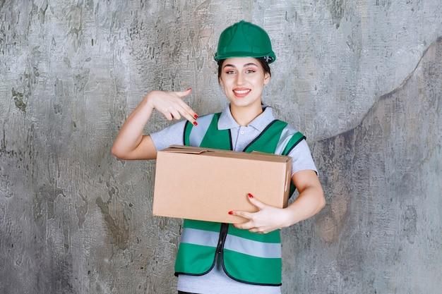 Ingenieurin im grünen helm mit einem karton
