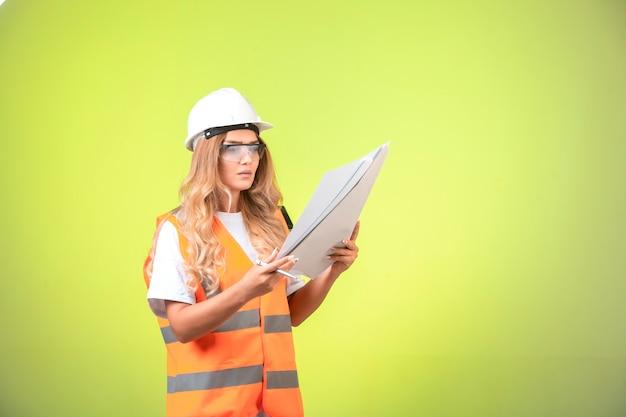 Ingenieurin im projektplan für helm und ausrüstung, der ihn hält und liest.