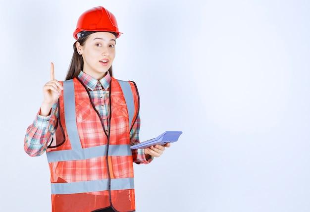 Ingenieurin im roten helm, die an taschenrechner arbeitet und eine idee hat.