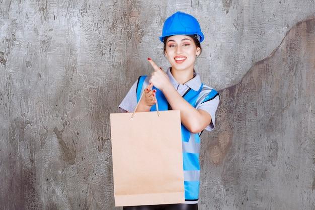 Ingenieurin in blauem helm und ausrüstung, die eine einkaufstüte aus pappe hält und auf irgendwo zeigt?