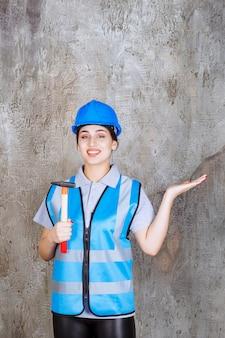 Ingenieurin in blauer ausrüstung und helm, die eine axt mit holzgriff hält.