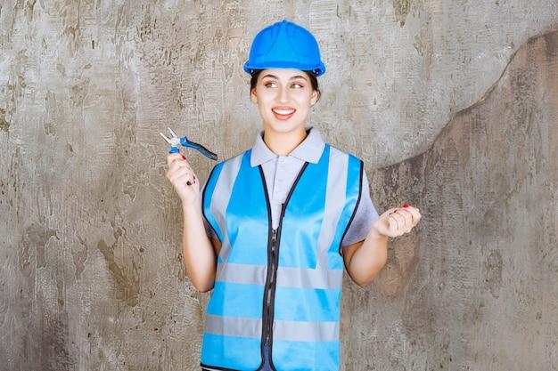Ingenieurin in blauer ausrüstung und helmhaltezange für reparaturarbeiten.