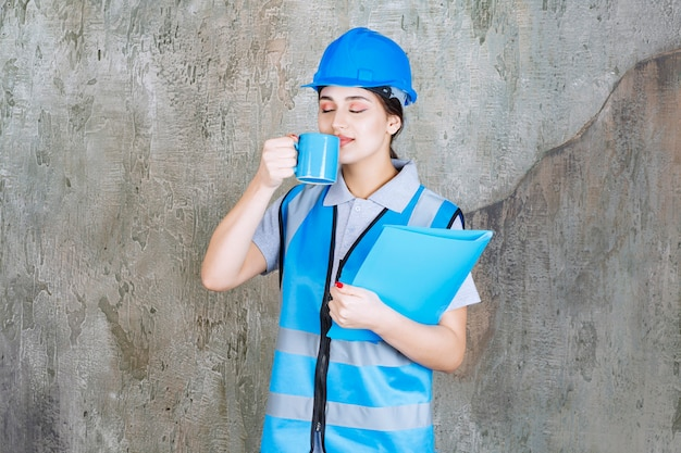 Ingenieurin in blauer uniform und helm, die eine blaue teetasse und einen blauen berichtsordner hält und das produkt riecht