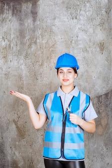 Ingenieurin in blauer uniform und helm, die eine metallzange zur reparatur hält und die betonwand dahinter zeigt
