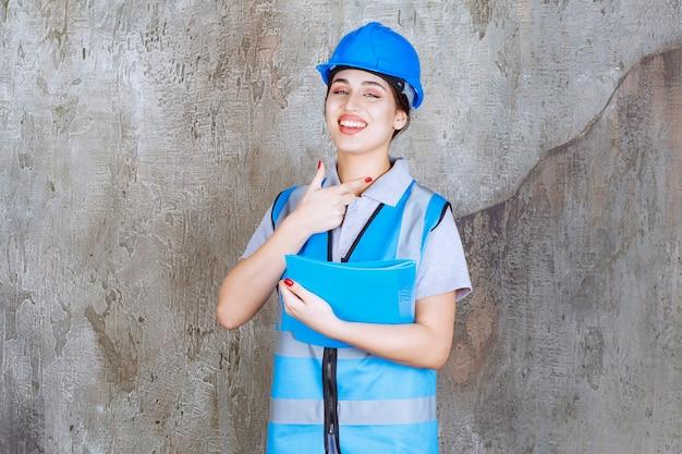 Ingenieurin in blauer uniform und helm, die einen blauen berichtsordner hält und auf jemanden zeigt.