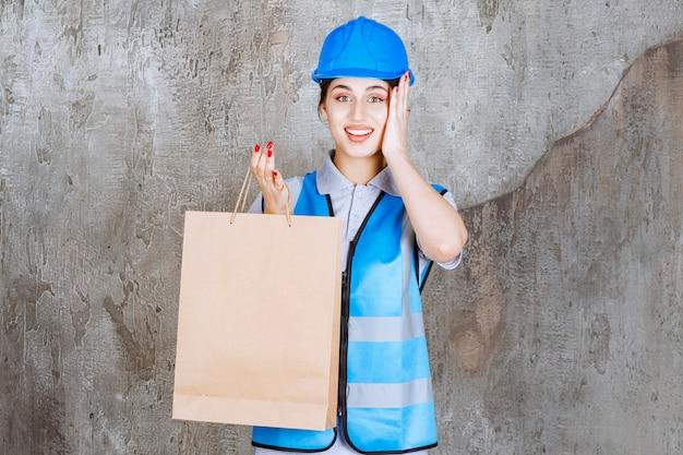 Ingenieurin in blauer uniform und helm hält eine einkaufstasche und sieht überrascht aus.