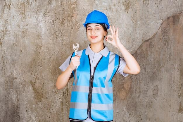 Ingenieurin in blauer uniform und helm hält einen metallschlüssel.