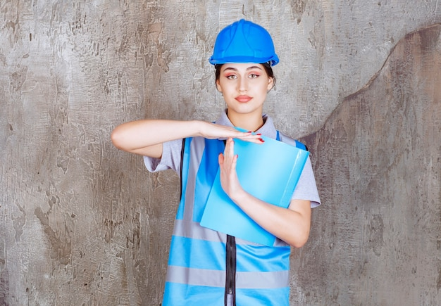 Ingenieurin in blauer uniform und helm mit blauem berichtsordner