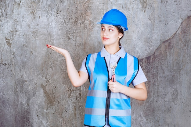 Ingenieurin in blauer uniform und helm mit einem metallischen schraubenschlüssel.