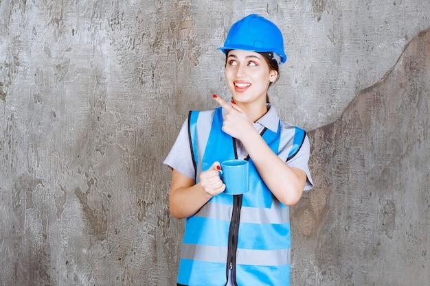 Ingenieurin in blauer uniform und helm mit einer blauen teetasse.