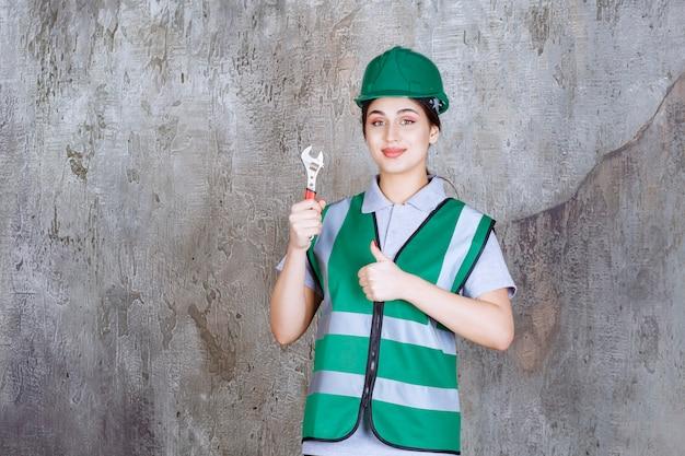 Ingenieurin in grünem helm, die einen metallschlüssel für reparaturarbeiten hält und ein freudenhandzeichen zeigt