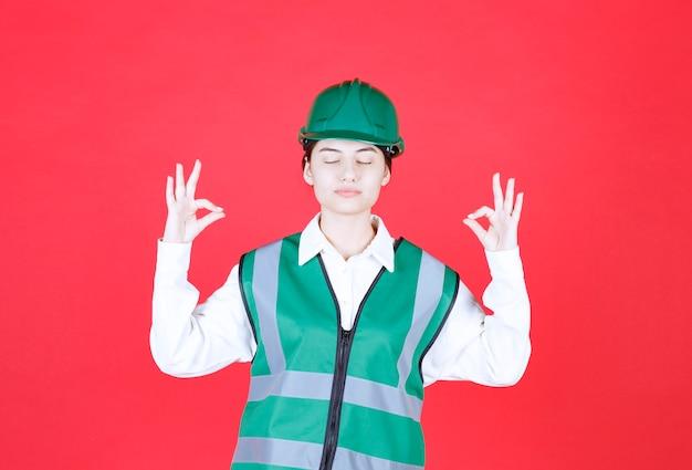 Ingenieurin in grünem helm und uniform, die meditation macht
