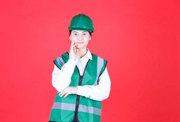 Ingenieurin in grünem helm und uniform sieht verwirrt und nachdenklich aus