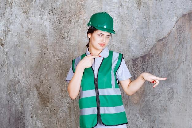 Ingenieurin in grüner uniform und helm auf der rechten seite.