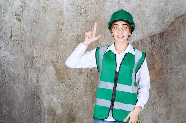 Ingenieurin in grüner uniform und helm, die auf einer betonwand steht und nach oben zeigt