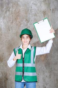 Ingenieurin in grüner uniform und helm, die die projektliste demonstriert und den daumen nach oben zeigt.
