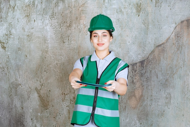 Ingenieurin in grüner uniform und helm, die einen blauen projektordner hält und zur überprüfung anbietet.