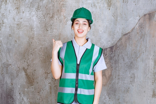 Ingenieurin in grüner uniform und helm, die etwas dahinter zeigen.