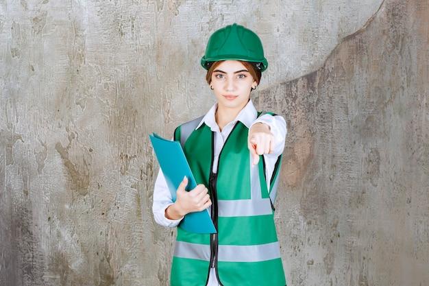 Ingenieurin in grüner uniform und helm hält einen grünen projektordner und ruft die person voraus.