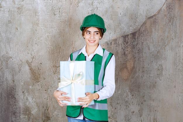 Ingenieurin in grüner uniform und helm mit blauer geschenkbox