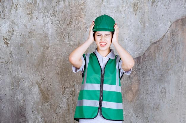 Ingenieurin in grüner uniform und helm sieht verängstigt und verängstigt aus.