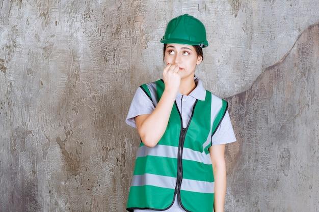 Ingenieurin in grüner uniform und helm sieht verängstigt und verängstigt aus