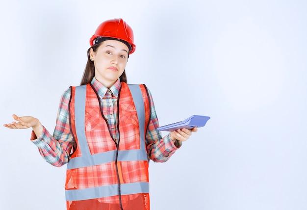Ingenieurin in rotem helm, die am taschenrechner arbeitet und verwirrt oder begeistert aussieht.
