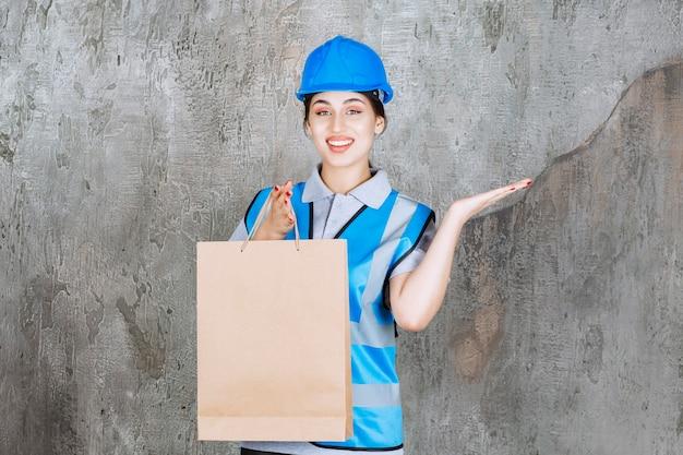 Ingenieurin mit blauem helm und ausrüstung, die eine einkaufstüte aus pappe hält und auf irgendwo zeigt?