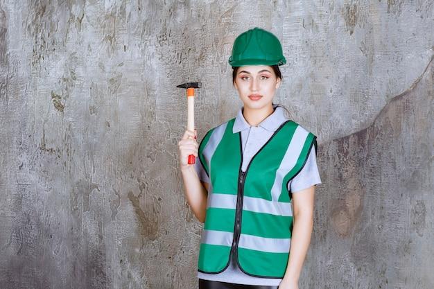 Ingenieurin mit grünem helm, die eine holzaxt für reparaturarbeiten hält