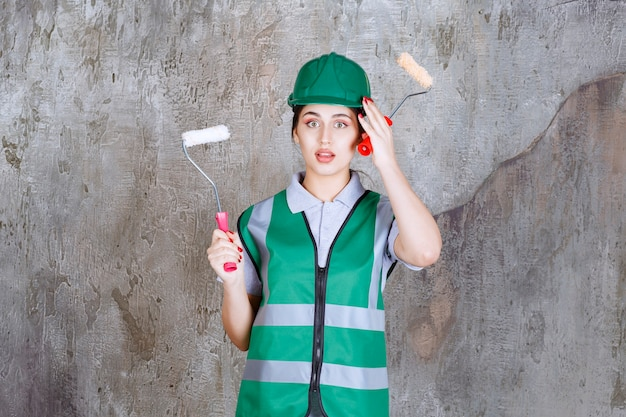 Ingenieurin mit grünem helm, die eine trimmrolle für die wandmalerei hält und über neue methoden nachdenkt