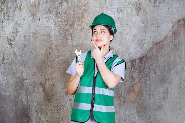 Ingenieurin mit grünem helm, die einen metallschlüssel für reparaturarbeiten hält und über neue ideen nachdenkt