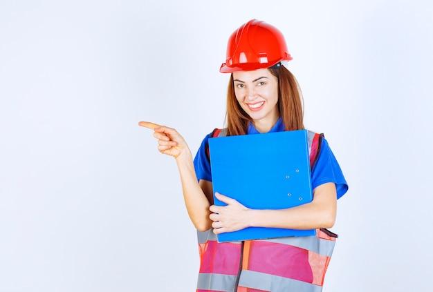 Ingenieurin mit rotem helm, die einen blauen projektordner hält und jemanden oder etwas vorstellt.