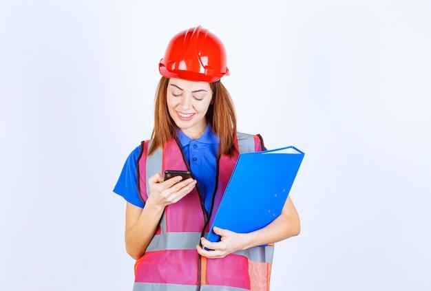 Ingenieurin mit rotem helm, die ihre nachrichten überprüft oder einen videoanruf tätigt.