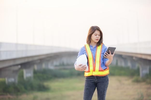 Ingenieurin mit weißem sicherheitshelm, der tablette hält, die auf baustelle steht