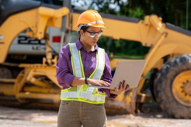 Ingenieurinnen benutzen laptop auf der baustelle. immobilienbauprojekt mit baufahrzeug am arbeitsbereich.