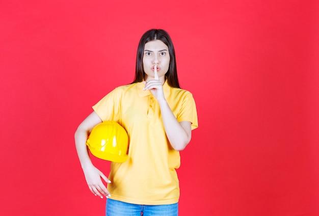 Ingenieurmädchen im gelben dresscode, das einen gelben schutzhelm hält und um unterschrift bittet.