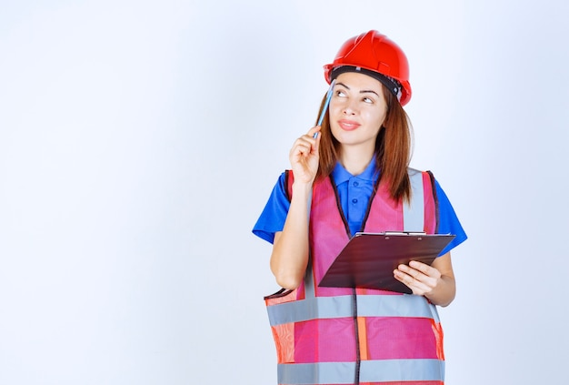 Ingenieurmädchen in uniform, das eine checklistendatei hält und denkt.
