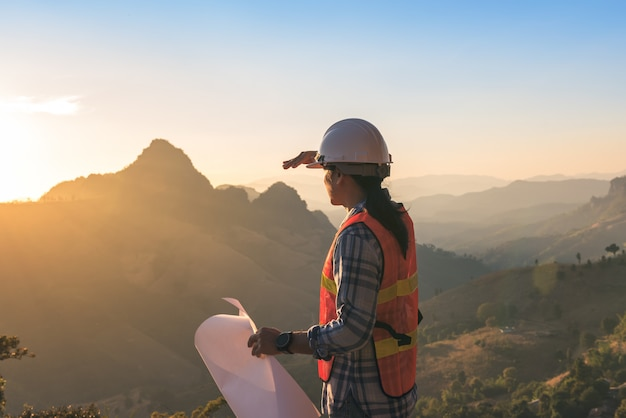 Ingenieurmann, der blaupause hält und sonnenuntergang auf gebirgsbereichshintergrund betrachtet