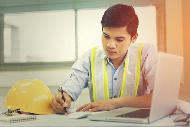 Ingenieurmann, der mit dem laptop und plänen ein bauprojekt skizzieren arbeitet