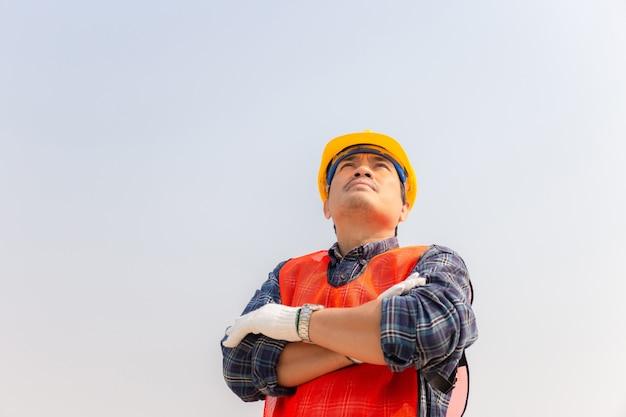 Ingenieurmann, der projekt auf baustelle prüft und plant, mann, der in den himmel schaut