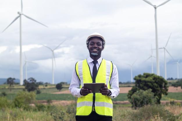 Ingenieurmann, der tablette mit windkraftanlage hält
