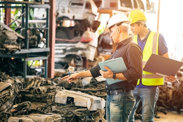 Ingenieurmitarbeiter, der mit dem manager zusammenarbeitet, der den lagerbestand in der garage für gebrauchte motorteilelager überprüft