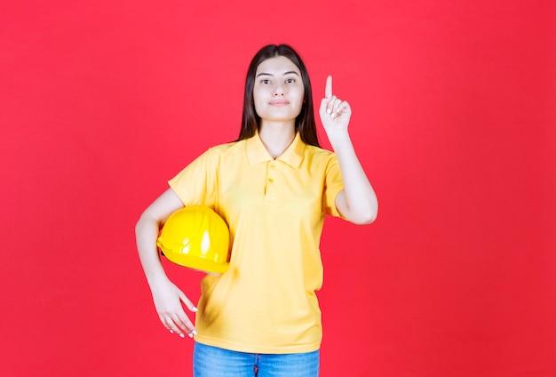 Ingenieursmädchen im gelben dresscode, das einen gelben schutzhelm hält und irgendwo zeigt