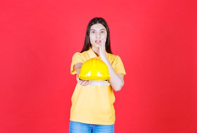 Ingenieursmädchen in gelber kleiderordnung, das einen gelben schutzhelm hält und erschrocken und verängstigt aussieht