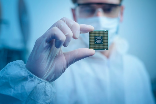 Ingenieursmann im sterilen anzug hält mikrochip mit symbolen in moderner designfabrik, futuristischem und künstlichem intelligenzkonzept